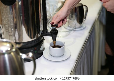 Woman's hand pressing the button on a coffeemaker. A white cup standing beneath. Preparing fresh espresso coffee.