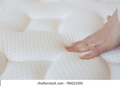 Woman's hand pressing a mattress