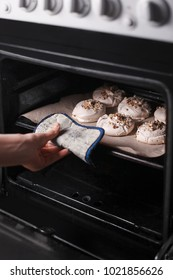 woman's hand pulls out meringue with walnuts  on baker paper from oven. close-up.