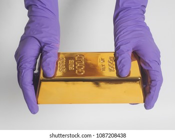 Woman's hand in purple gloves holding a gold bullion
