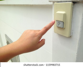 Woman's hand push the doorbell in front of house. Doorbell for guest in front of the house.