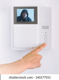 Woman's Hand Pushing a Button on a Security Pad with a pixelated image of a Suspicious Man on the Screen