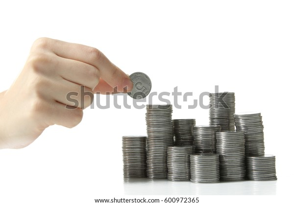 A woman's hand puts a coin on a tower of coins isolated on a white background.
