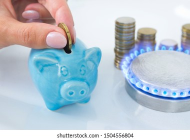 Woman's hand puts a coin in a piggy bank near the blue flame of domestic gas in the kitchen stove. The symbolic image of saving natural gas, paying for gas consumed, energy efficiency at home.