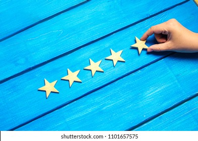 A woman's hand puts the fifth star. Quality status is five stars. A new star, achievement, universal recognition.The critic determines the rating of the restaurant, hotel, institution. Quality mark.