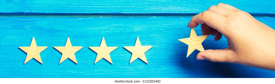 A woman's hand puts the fifth star. Quality status is five stars. A new star, achievement, universal recognition.The critic determines the rating of the restaurant, hotel, institution Quality mark.
