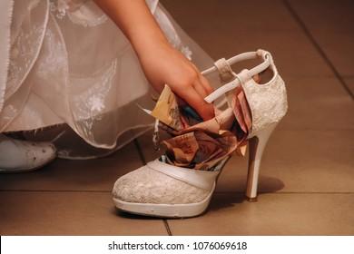 A woman's hand puts money in elegant shoe