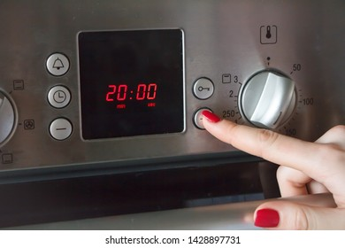 A womans hand puts on the oven a time of 20 minutes and a temperature of 180 degrees for making apple pie, copyspace
