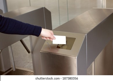 Woman's hand puts a white plastic card to the reader access control space closeup