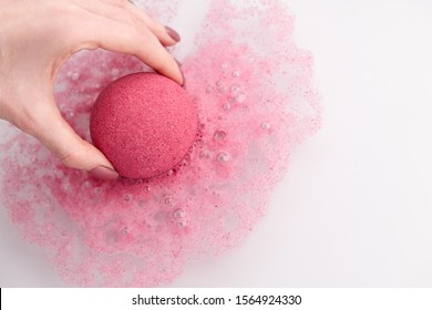 Woman's hand putting bath bomb into water, copy space