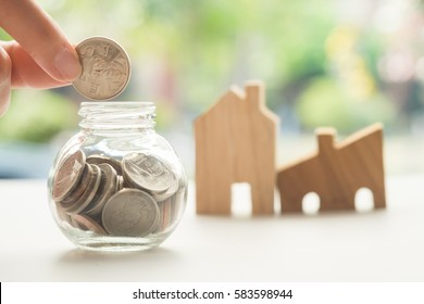 Woman's hand putting coin into glass of bottle for saving money and the wooden house as background. Concept for property ladder, mortgage and real estate investment .