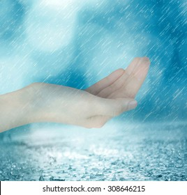 Woman's hand with rain. Conceptual image of sharing, giving, offering, taking care and protection