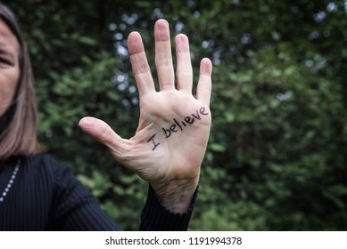 Womans hand raised with I believe written in marker supporting victims of abuse