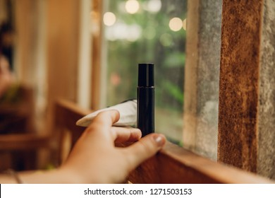 Woman's hand reaching essential oils roll on perfume in a dark brown glass bottle among nature background. Luxury treatment. Beauty blog, blogging concept Warm color filter, toned image