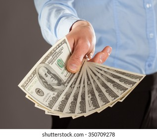 Woman's hand reaching out money on grey background