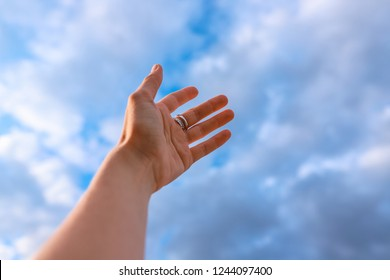 Woman's hand reaching to towards blue sky. Dream and fly, you can.