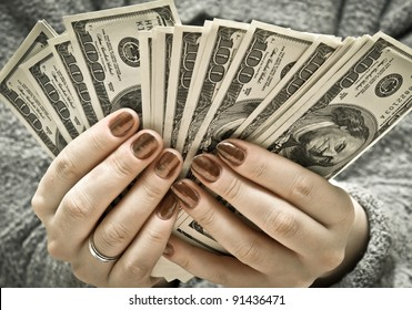 Woman's hand recount bundle of dollars
