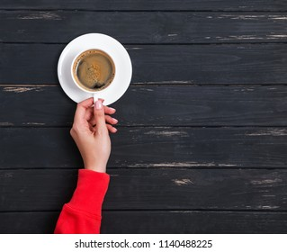 Woman's hand in red clothing holding a cup of coffee on the black wooden background, top view