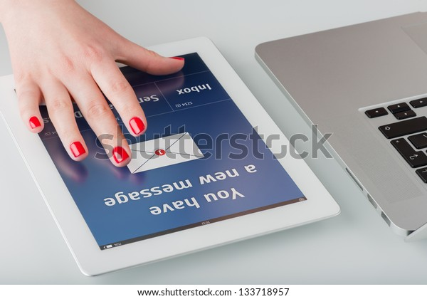 Woman's hand with red manicure opens a new email message on a tablet computer.