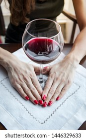 a woman's hand with a red nail holds a goblet with red wine, a large glass of red wine on a white napkin on the table in the restaurant.
