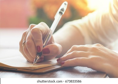 woman's hand with red nails writing some message note or letter to notebook by pen at sunny day