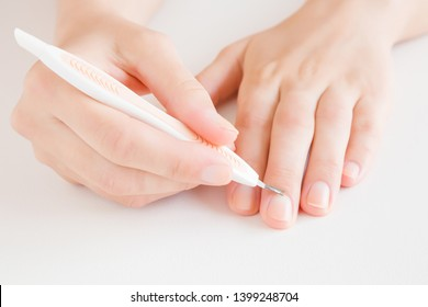 Woman's hand removing nail cuticle with pusher stick on light gray table. Care about dry, overgrown cuticle. Front view. Closeup.
