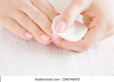 Woman's hand removing pink nail polish with white cotton pad on white towel. Front view. Closeup.