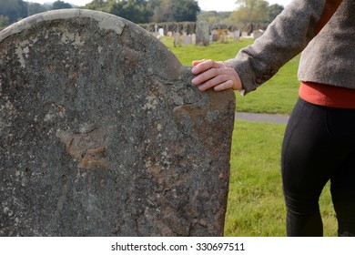 Woman's hand resting on an anonymous headstone in a rural graveyard