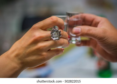 Woman's hand with a ring and a male hand holding a glass of vodka while cheers