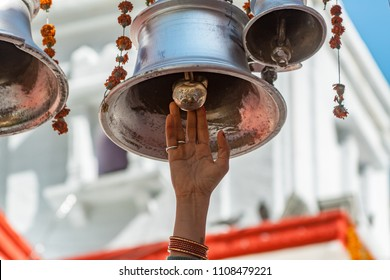 A woman's hand rings a temple bell in the temple of Ganga Devi at Gangotri in India.