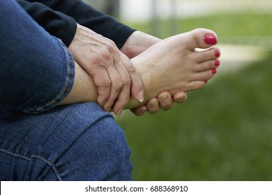 A woman's hand rubbing the sole of her foot while sitting in a chair outdoors with shallow depth of field