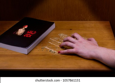 Woman's hand scratching a bedside table, where there is a book about wild sex