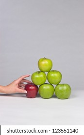 Woman's hand selecting the only red apple from a stack of mostly green apples