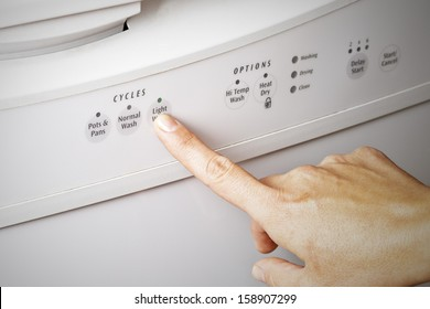 A woman's hand setting the dishwasher cycle to light wash, energy efficient concept