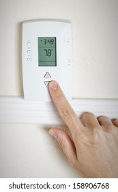 A woman's hand setting the room temperature on a modern digital programmable thermostat