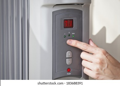 A woman's hand setting the room temperature on a modern digital programmable oil heater radiator