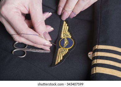 Woman's hand sewing pilot wings onto a airline uniform jacket