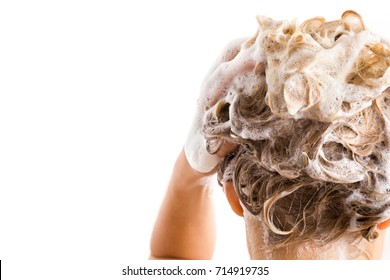 Woman's hand with shampoo washing hair isolated on the white background. Cares about a healthy and clean hair. Beauty salon. Empty place for a text.