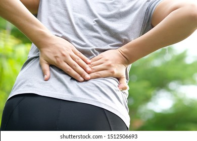 Woman's hand She is caught at the waist and her back is painful at the back in the park. Cause of the exercise.