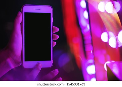Woman's hand showing smartphone screen in neon blue and pink lights