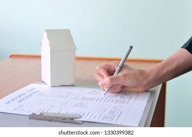 Woman's hand signing mortgage loan document as  home ownership. Mortgage and real estate property investment. Buying a home by applying loan program offer.