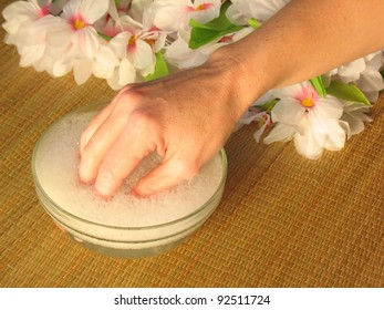Woman's hand soaking in a bowl of soapy water before getting a manicure at an elegant spa.