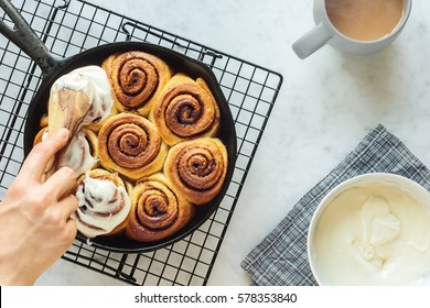 Woman's Hand Spreading Frosting Across Freshly Baked Cinnamon Rolls in Cast Iron Skillet