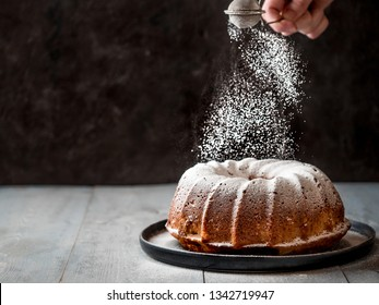 Woman's hand sprinkling icing sugar over fresh bundt cake. Powder sugar falls on fresh perfect bundt cake. Copy space for text. Ideas and recipes for breakfast or dessert. Black background