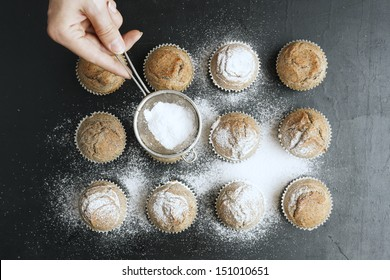 Woman's hand sprinkling icing sugar over fresh muffins.