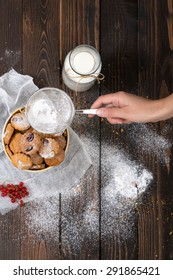Woman's hand sprinkling icing sugar over cookies. Selective focus and small depth of field.