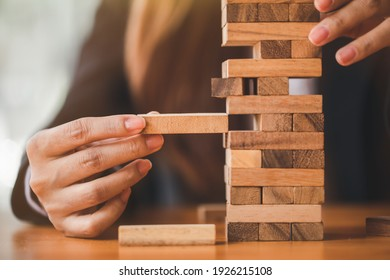 Woman's hand stacking wooden blocks  on a tower,. Business Planning,risk, strategy,development and Alternative risk concept.