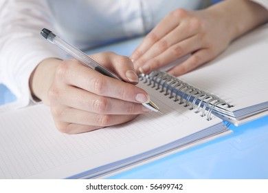 Woman's hand starting to make notes in a diary