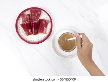 woman's hand stirring a cup of coffee with rose apples on marble table. top view.