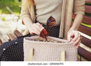 Woman's hand with sunglasses and knitted handbag. Stylish woman in gray shirt and knitted beige jacket sitting in the park with beige handbag. Street look, casual fashion concept